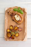 Steak and baked potatoes with garlic. Steak with cream sauce and baked potatoes with garlic, served on a wooden board, on a white wooden table royalty free stock photography