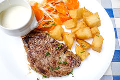 Steak beef meat with tomato and french fries Royalty Free Stock Photos