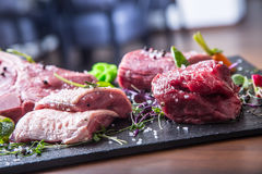 Steak.Beef steak.Meat.Portioned meat.Raw fresh meat.Sirloin steak.T-Bone steak. Flank steak. Duck breast. Vegetable decoration. Stock Image