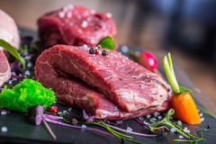 Steak.Beef steak.Meat.Portioned meat.Raw fresh meat.Sirloin steak.T-Bone steak. Flank steak. Duck breast. Vegetable decoration. Portioned meat prepared for royalty free stock photos