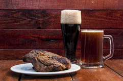 steak and beer on a wooden background royalty free stock photos