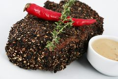 Steak in black spices and breadcrumbs. With hot pepper and a sprig of rosemary. stock image