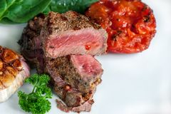 Steak with blood medium rare with a side dish of tomatoes and vegetables with spinach sauteed in a homemade pan on a stock photography