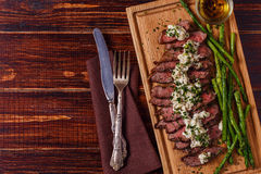 Steak with blue cheese sauce served with asparagus. Royalty Free Stock Images