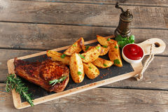 Steak on the bone with baked potatoes Royalty Free Stock Images