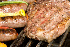 Steak and bratwurst on barbecue Stock Images