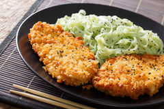 Steak in breadcrumbs Panko and green noodles with sesame close-u Stock Photos