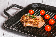 Steak and cherry tomatoes in a pan. Beef steak on the grill pan with spices and tomatoes Stock Photography