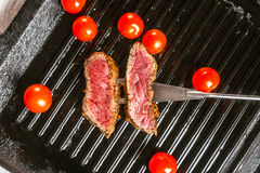 Steak and cherry tomatoes in a pan. Beef steak on the grill pan with spices and tomatoes Royalty Free Stock Photo