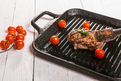 Steak and cherry tomatoes in a pan. Beef steak on the grill pan with spices and tomatoes Royalty Free Stock Photos