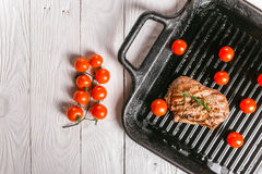 Steak and cherry tomatoes in a pan. Beef steak on the grill pan with spices and tomatoes Stock Images