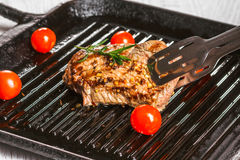 Steak and cherry tomatoes in a pan. Beef steak on the grill pan with spices and tomatoes Stock Image