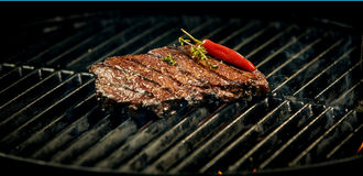 Steak with chilli pepper. Fried steak with chilli pepper close-up on barbecue grid Royalty Free Stock Photo