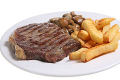 Steak & Chips. Seasoned sirloin steak with crinkle-cut fries and sauteed mushrooms on a white ceramic plate Royalty Free Stock Photos