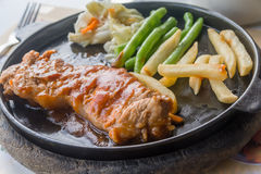 Steak and chips on black plate Stock Photography