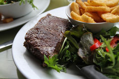 Steak and chips meal, with salad. Meal of steak, salad, and hot chips Stock Images