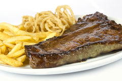 Steak, chips and onion rings Stock Photography