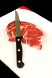 Steak on chopping board Stock Images