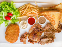 Steak combo. Witch beef chicken fish and salad in white plate royalty free stock images