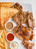 Steak combo. Witch beef chicken fish in white plate royalty free stock images