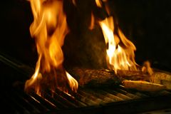 Steak cooking. On wood fired flame grill in Restaurant stock photography