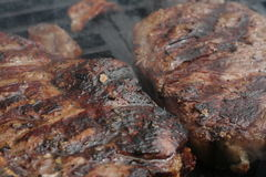 Steak cooking on flame grill Stock Photo