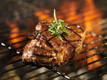 Steak cooking over flaming grill Royalty Free Stock Images