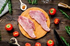 Steak cooking with meat and spices on wooden background top view. Steak cooking with raw meat, tomato and spices on wooden desk background top view Stock Image