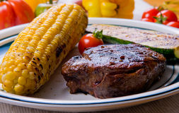 Steak and corn on the cob. Fresh steak with corn on the cob, zucchini and tomato Stock Image