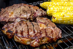 Steak and Corn on Hot Grill Royalty Free Stock Image