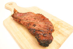 Steak on a cutting board. Isolated photo of a steak on a cutting board on white Royalty Free Stock Photo