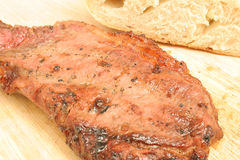 Steak on cutting board upclose. Isolated photo of a steak on cutting board upclose on white Royalty Free Stock Photos