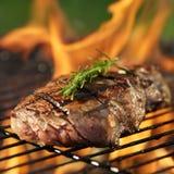 Steak, das über loderndem Grill kocht Lizenzfreies Stockfoto