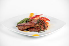 Steak decorated with vegetables on a plate Royalty Free Stock Images