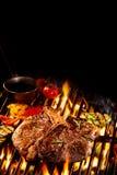 Steak des förmigen Knochens auf loderndem Grill mit Kopienraum Stockfotografie