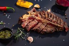 Steak des Porterhouseförmigen knochens wird geschnitten auf einem Stück mit gegrilltem Mais, Soße, Paprika, Rosmarin, Salz, Knobl lizenzfreie stockfotografie