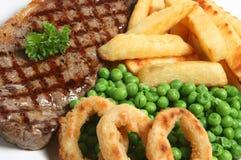 Steak Dinner. Sirloin steak dinner with fries, peas and onion rings Stock Photos