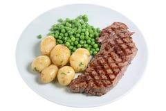 Steak Dinner. Juicy Sirloin steak with new potatoes and garden peas Stock Photography