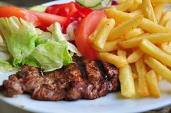 Steak dinner. Pork steak dinner with french fries and fresh vegetables Stock Photography