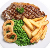 Steak Dinner. Sirloin Steak with fries, peas and onion rings Royalty Free Stock Photography
