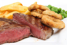 Steak Dinner. Rare ribeye steak with chips, onion rings and peas Royalty Free Stock Photo