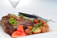 Steak Dinner. T-bone steak dinner served with grilled vegetables Royalty Free Stock Photo