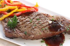 Steak Dinner. Grilled strip or porterhouse grain-fed beef steak, with colorful vegetables and an onion gravy Royalty Free Stock Images