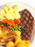 Steak dinner from above. A traditional pub-grub style British meal of rump steak, mixed veg, mashed and roasted potatoes and Yorkshire pudding, viewed from above stock image