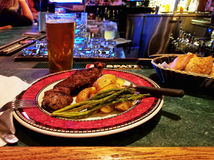 A steak dinner plate, with potatos, asparagus, and a glass of be royalty free stock image