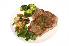 Steak dinner with sides. T-Bone steak dinner with sides of potatoes and broccoli isolated on white Stock Photo