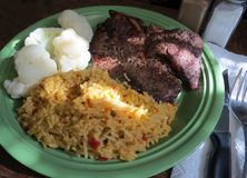 Steak Dinner. Sunlight from a window falls on a plate with broiled steak, Mexican rice and cauliflower royalty free stock image