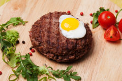 Steak egg cutlet on a wooden board tomatoes arugula bright beautiful quail beef pork Stock Images