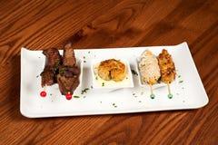Steak, Fischfrikadelle und Huhn Stockbilder