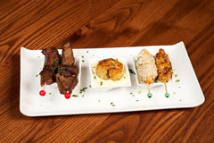 Steak, fish cake and chicken. Continental tapas or appetizers consisting of steak, fish cake and sesame seed chicken with skewers or rectangular white plate Stock Images